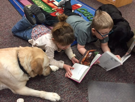 Therapy dogs Gracie (left) and Riley (right) listen to students read at Palmer Elementary School in Windsor.