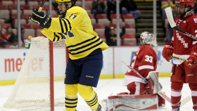 Michigan's Zach Hyman (11) celebrates his first period goal against Wisconsin's Joel Rumpel (33) during an NCAA college hockey game in the Big Ten Conference tournament Thursday, March 19, 2015, in Detroit.