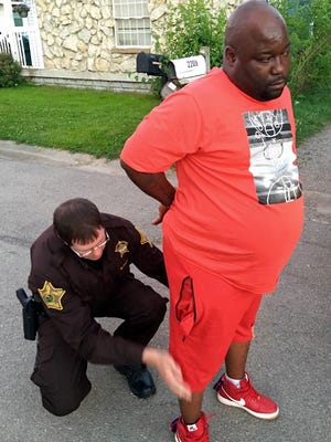 """A deputy takes Pierre Jerome """"Boo"""" Phillips, 45, into custody during a Thursday-night heroin raid at a house on East 18th Street, June 2, 2016."""