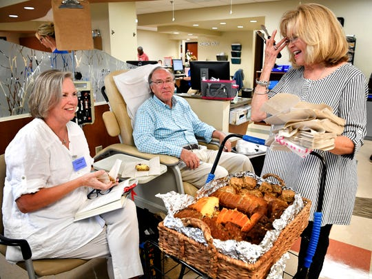 Marilyn and Fred Keith receive a smile and some homemade sweet bread from Barbara Baker who has made a ministry out of her baked goods for the past 12 years by handing them out as people go through cancer treatments Wednesday Aug. 2, 2017, in Nashville.