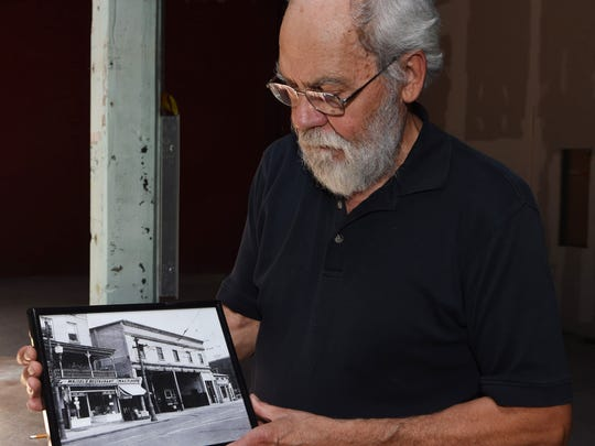 Roy Budnik, a geologist and Town of Poughkeepsie resident, holds a 1905 photograph of 489 Main Street in the City of Poughkeepsie.