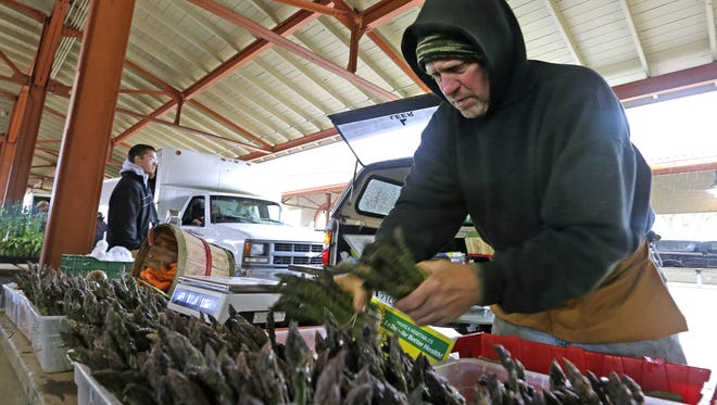 David Witte, of West Bend, Wis., sells early-season produce asparagus and spinach from his farm at a farmers market. Western states are struggling through a drought which is affecting the agriculture industry because of its reliance on irrigation.