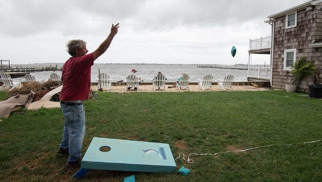 David Harper plays cornhole at his home in Oak Orchard, east of Millsboro, as Tropical Storm Hermine moves off the coast of Delaware.