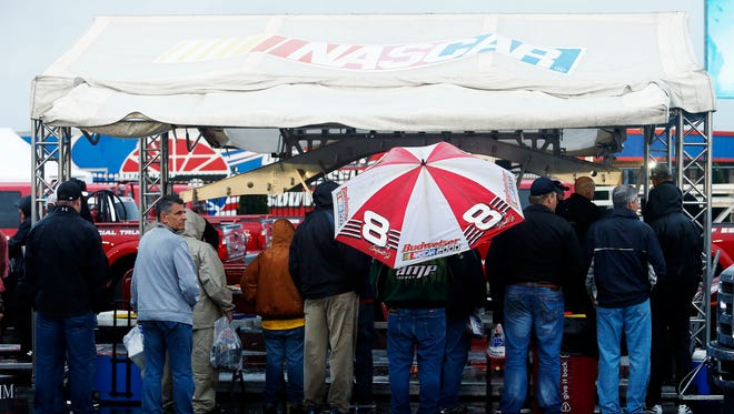 NASCAR fans watch cars go through inspection in the rain Saturday at Charlotte Motor Speedway.
