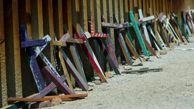 Crosses rest against the U.S.-Mexico border fence in Nogales, Sonora.