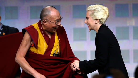 The Dalai Lama greets Lady Gaga before an interview