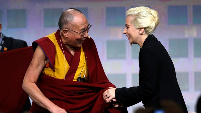 The Dalai Lama greets Lady Gaga before an interview  at the U.S. Conference of Mayors in Indianapolis.