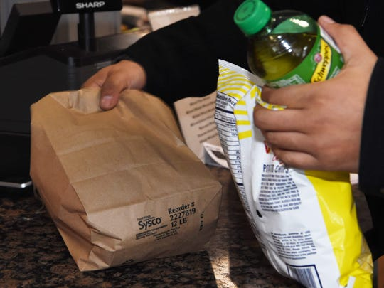 A customer gets his sandwich in a paper bag at Russo's