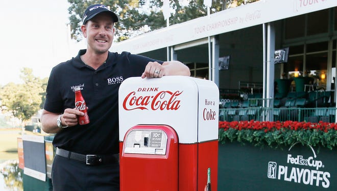 Henrik Stenson poses with an antique Coke machine on the 18th green after winning the TOUR Championship by Coca-Cola and the FedExCup Playoffs at East Lake Golf Club.