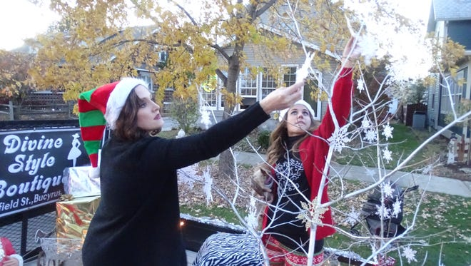 Kelly Redmon, left, and Tessa Starner hang snowflakes from their float Friday before the Bucyrus Santa Parade. Thousands of spectators lined Sandusky Avenue for the event.
