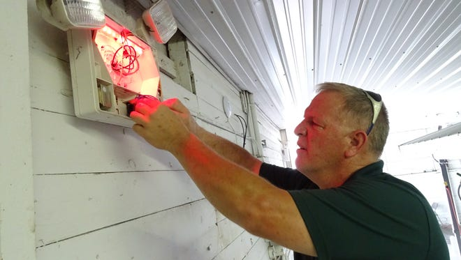 Roger Brown of A&E Fire and Safety Services, Bucyrus, tests the emergency lights Wednesday in the Whetstone Building at the Crawford County Fairgrounds.