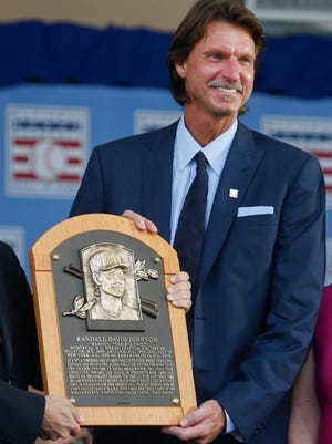 National Baseball Hall of Fame inductee Randy Johnson holds his plaque during an induction ceremony at the Clark Sports Center on Sunday, July 26, 2015, in Cooperstown, N.Y.