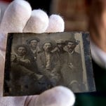 This tintype, believed to be from the early 1880s, shows five men in hats with whiskey, their faces later rouged with pastels as was common in that era.