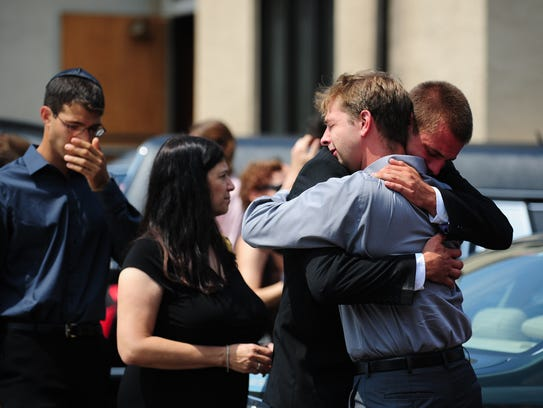 Unidentified mourners comfort each other at the memorial