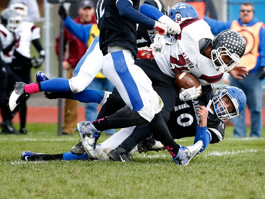 Express' Devon Torres is brought down by Blue Raiders quarterback Ben Clark on Saturday at  Horsehead.