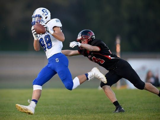 Sartell tight end Riley Hartwig pulls in a pass and is brought down by Rocori defensive back Will Matuska during the first half Friday in Cold Spring.