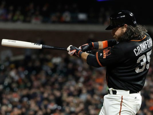 San Francisco Giants' Brandon Crawford (35) drives in a run with a single against the Oakland Athletics during the seventh inning of an exhibition baseball game Thursday, March 30, 2017, in San Francisco. (AP Photo/Marcio Jose Sanchez)