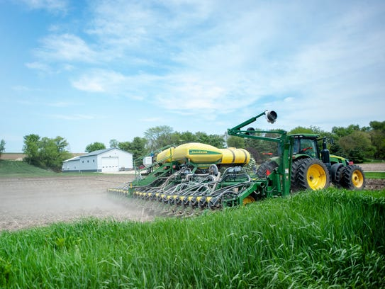 A planter plants soybeans in an untilled field near