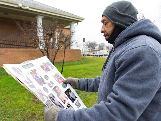 Tyson Henry's cousin, Dickie Wilmore of Dover, looks at memories of Tyson where family members gathered for a rally in front of the Dover Police Department on what would have been Tyson's 27th birthday.