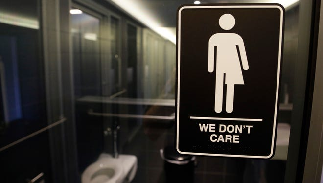 Signage hangs outside a restroom at 21c Museum Hotel in Durham, N.C.