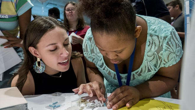 Sarah Jenkins, an associate with Kendra Scott (left), works with Marsheka Gallion on a necklace during Job-A-Palooza at Palm Beach State College in Palm Beach Gardens in this 2018 photo. The fast-paced job training event, hosted by The Arc of Palm Beach County, gives candidates the opportunity to learn about possible careers and meet potential employers that want to hire people with disabilities.