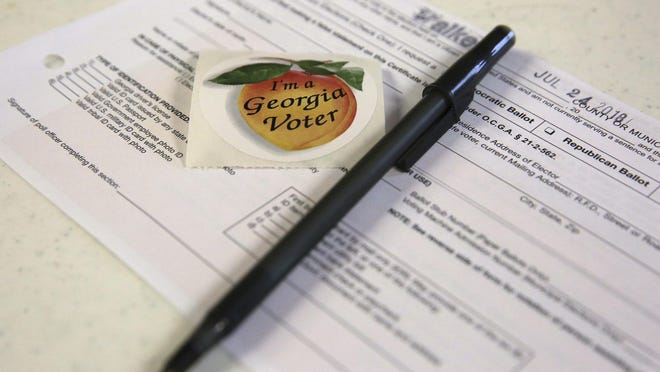 Paperwork and voting stickers sit out for voters of the Georgia primary election Tuesday, July 24, 2018 at the Chattanooga Valley Church of the Nazarene in Flintstone, Georgia.