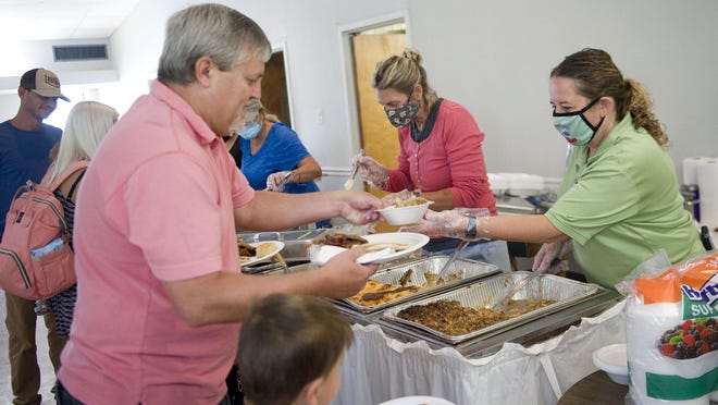 Melanie Matteson, right, Elks Lodge member and N.C. Apple Festival board member, serves fellow Elks Lodge member Barry Saltz a bowl of baked apples during the annual Elks Lodge Apple Breakfast on Sunday morning. All proceeds from the breakfast go toward funding the Elks Lodge's Christmas Charities service.
