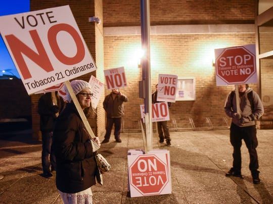People hold signs in opposition to a proposed tobacco ordinance Monday, Nov. 6, before the start of the St. Cloud City Council meeting at City Hall.