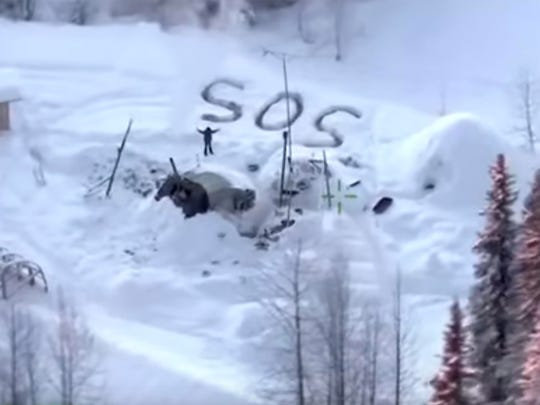 "A man waves with distress signal ""SOS"" outside Susitna Valley, Alaska, on Jan. 9. Alaska State Troopers rescued Tyson Steele, 30, who survived in a makeshift shelter after his remote cabin burned last month."