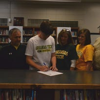 Yellville-Summit basketball standout Logan Lynch, third from left, signed a National Letter of Intent on Friday at the high school library, to play at Arkansas Tech University in Russellville.