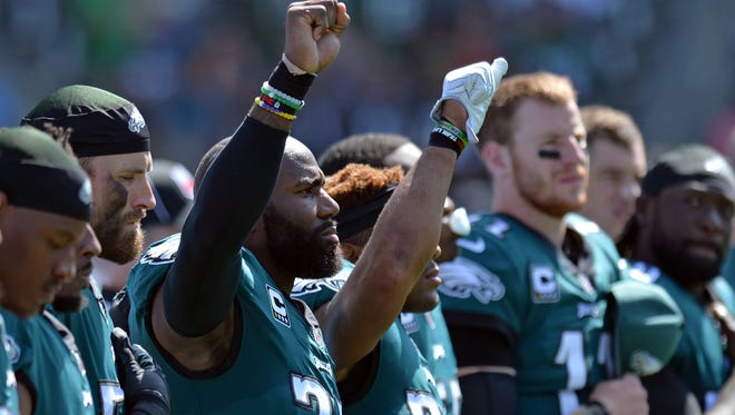 Philadelphia Eagles strong safety Malcolm Jenkins, left, and free safety Rodney McLeod raise their fists during the national anthem before an October game against the Chargers.