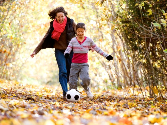Mid adult woman and her daughter playing with a soccer ball