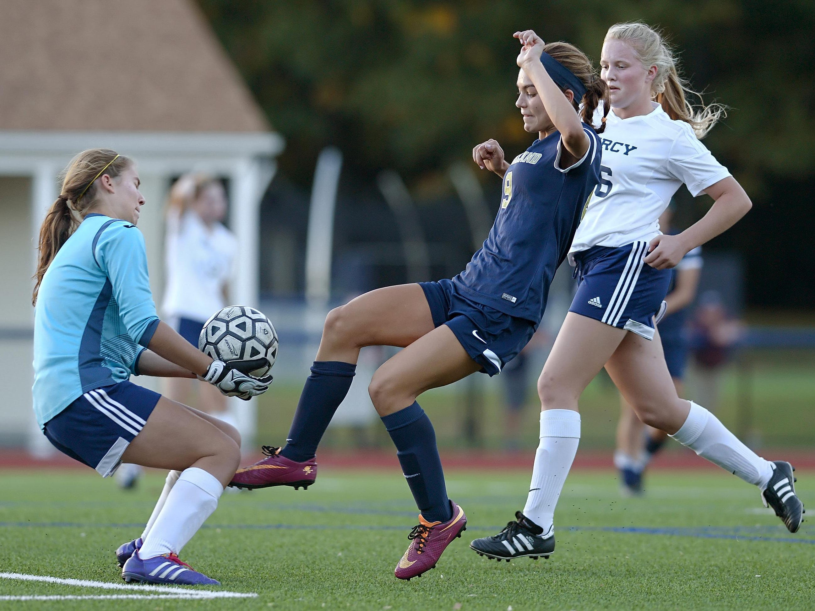 Mercy goalie Madeline Pizzo, left, grabs the ball as Pittsford Sutherland's Annie Hanna reaches for it.