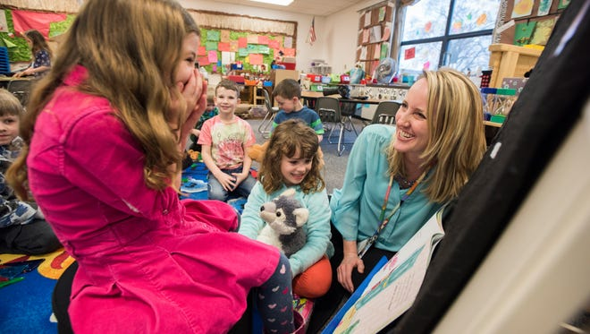 Teacher Angie Cain shares a laugh with Genevieve Dimick, 4, as they read a book together Monday, Mar. 27, during a preschool class at Morton Elementary School in Marysville.