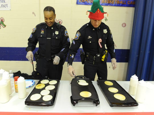 Master Corporal Johnny Saunders, left and Corporal John Truluck with the Wilmington Police Department cooks pancakes at their first annual breakfast for the youth at West Center City's Hicks Anderson Center on Saturday morning.