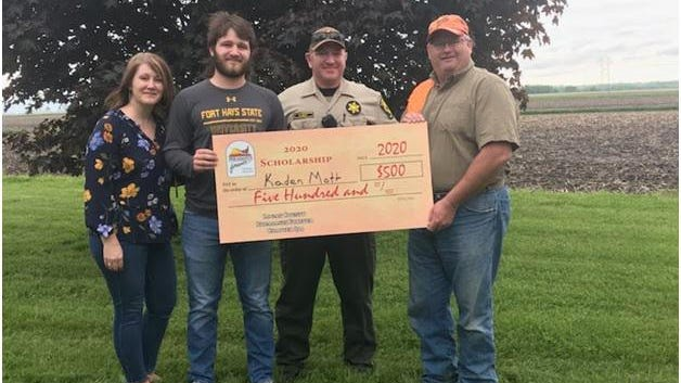 Kaden Mott  with his parents Deanne and Ryan.  Logan County Pheasants Forever Pres. Mark Miller