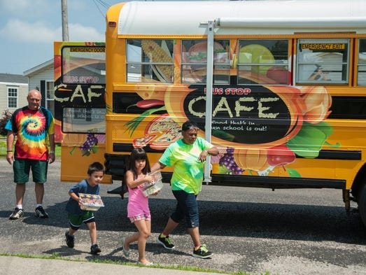 Joe Hillerich, left, watches as Mary Hull tells kids to give a lunch to their younger brother as they leave the Jefferson County School's new Bus Stop Cafe bus during a stop in the Autumn Lake Mobile Home Estate in Valley Station, Ky. July 2, 2014