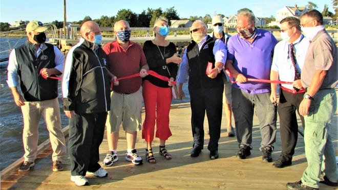 Town officials participate in a ribbon cutting ceremony signaling the end of the Barlows Landing dinghy dock construction project.