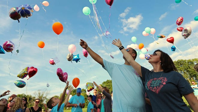 Kari Findley and Matt Rhinehart release balloons for Kari's daughter Emma Findley on what would have been her 14th birthday. Emma died a week before Christmas after a three-month battle with glioblastoma.