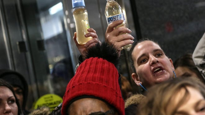 Nancy Burgher, right, of Flint holds a bottle filled with filtered City of Flint tap water from her home, while protesting in the lobby of the George W. Romney State Office Building in Lansing earlier this month. Burgher said the water tested at 11ppb for lead.