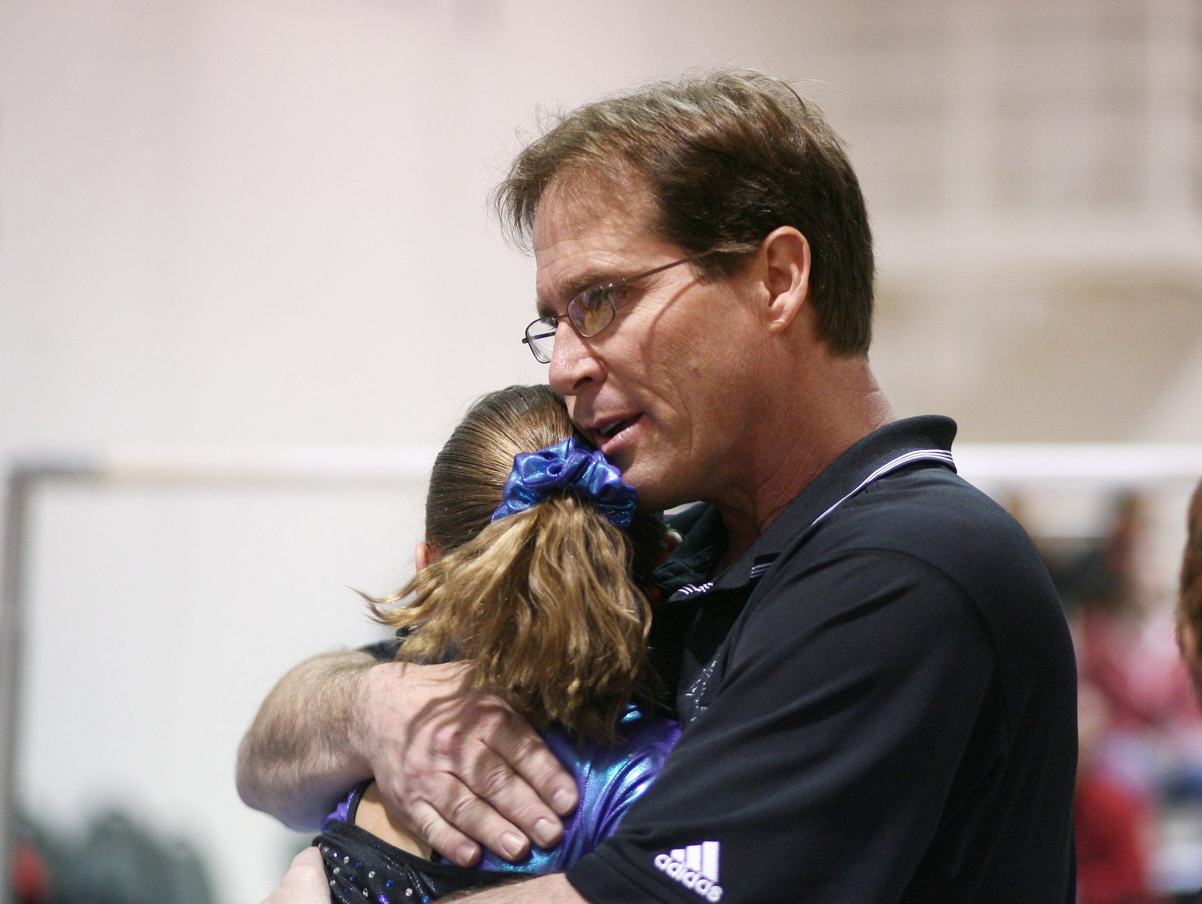 Jeffrey Bettman hugs a girl from the gym where he coached
