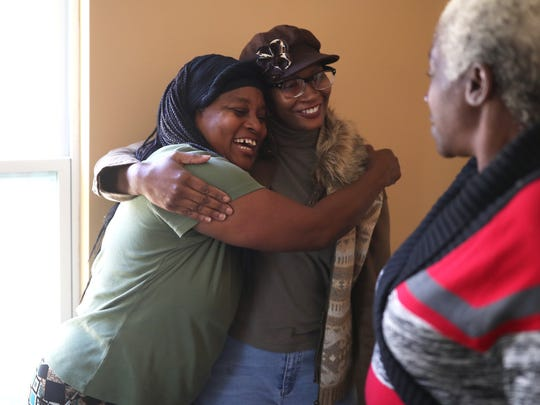 Deirdre Hazelton shares an embrace with her cousin Valerie Franklin as her friend Leslie Walker looks on while they explore Hazelton's new home in south Tallahassee on Thursday, March 8, 2018. Leon County worked to replace her original home with funds provided by a grant from the State Housing Initiatives Partnership, known as SHIP.