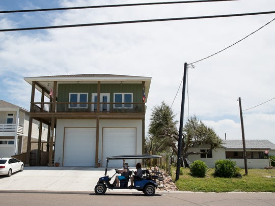 A golf cart passes by a more contemporary-styled home on Station Street in March. Port Aransas community leaders and residents are in talks on how the city should rebuild, including whether Old Town — a designated historic district — should put into place older-styled design standards for homes.