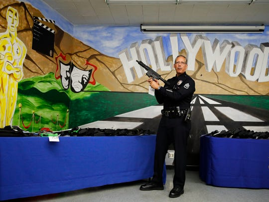 Los Angeles Detective Ben Meda shows a firearm during a news conference at the Hollywood community police station on Thursday. More than 40 firearms were seized in a recent joint task force operation, authorities said Thursday.