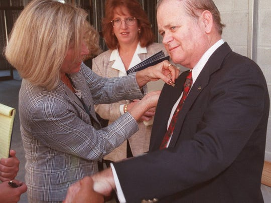 Joanna Hogan pins a Florida Gulf Coast University pin on Ben Hill Griffin III after a dedication ceremony naming a building after him.