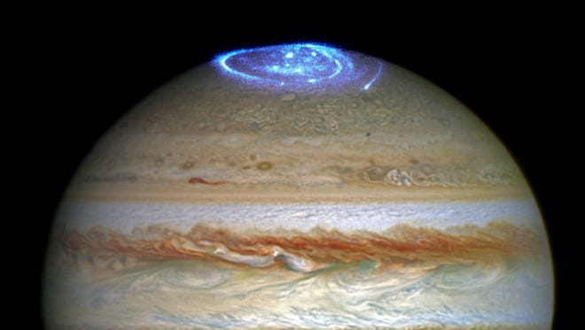 Jupiter's Red Spot and an aurora highlight the solar system's largest planet.