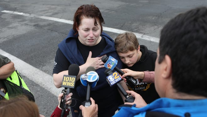 A parent with her child who was not involved in the accident speaks with the media at East Brook Middle School.