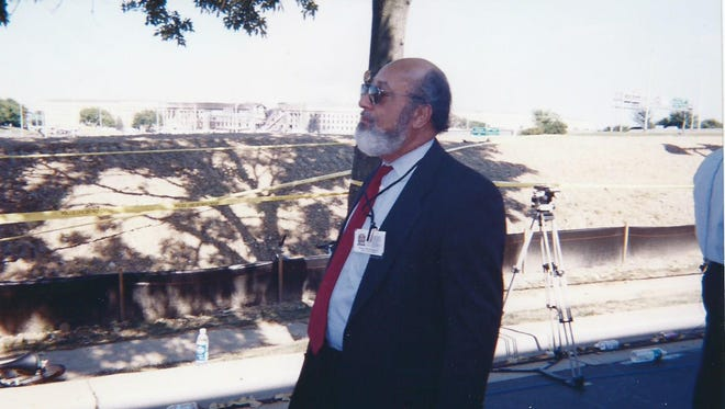 Glenn Flood was a press officer at the Pentagon when the U.S. came under attack on Sept. 11, 2001. A large hole in the side of the Pentagon where the plane hit can be seen in the background.