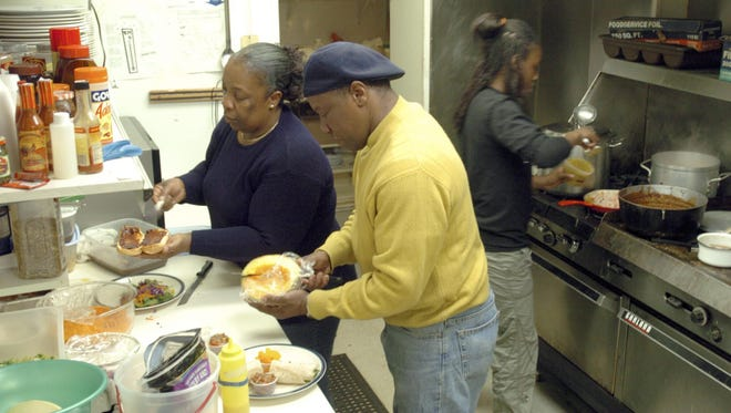 Joy and Jimmy Thomas, left, prepare plates of food while their granddaughter, Gabriella Myrie, tends to items on the stove at Jamaican Kitchens in Wisconsin Rapids.