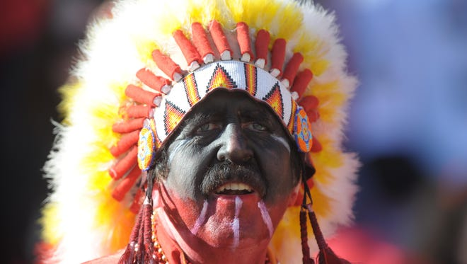 A Kansas City Chief fan dons face point and a Native American headdress